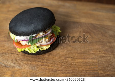 Classic black Burger. Tasty and fastfood burger meal on the table