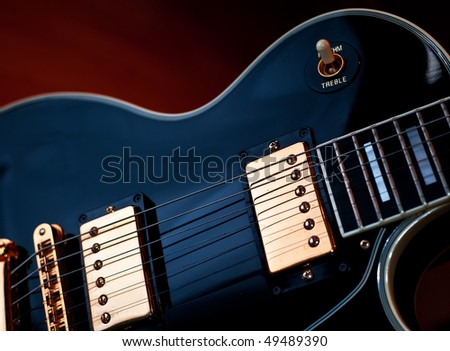 Classic black Les Paul rock and roll or jazz style guitar. Soft blue lighting on guitar and warm background light creates stage or studio performance atmosphere.