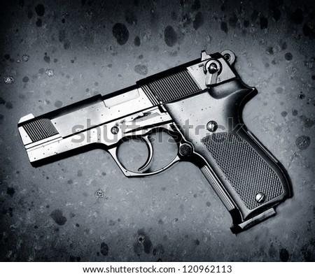 classic black pistol on rusty metal - stock photo