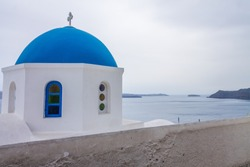 Classic blue dome from Oía, Santorini Island. Ocean view in the background on cloudy day with copy space.