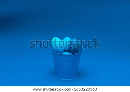 classic blue easter eggs in bucket. monochromatic composition. negative space