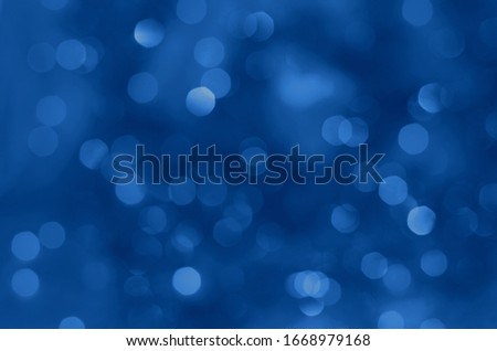 Classic blue lights bokeh background, Chrismas lights bokeh. Classic blue abstract background. Blurred and glowing lights. Lens effect from lighting spots. Classic blue color of the year 2020 concept.