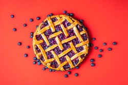 Classic blueberry pie with a lattice crust and fresh fruits, fresh from oven, on a red background. Top view of blueberries tart. Traditional dessert.