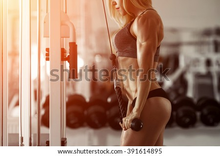 Stock Photo Classic bodybuilding. Muscular blonde fitness woman doing exercises in the gym. Fitness - concept of healthy lifestyle. Fitness woman in the gym. Crossfit woman. Bodybuilder woman in the gym.