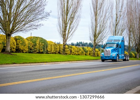 Classic bonnet commercial transportation pro American big rig blue long haul semi truck tractor driving on the road with trees and bushes for timely arrive to warehouse for loaded trailer #1307299666