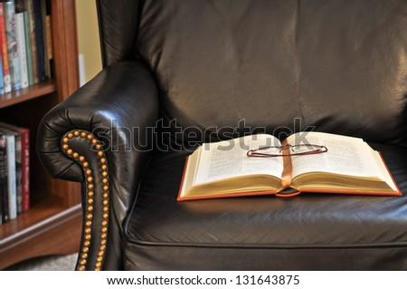 Classic book on leather reading arm chair in library room