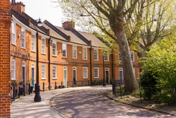 Classic British crescent with restored Victorian red brick houses on a local road with small garden in front