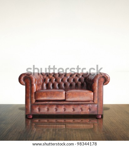 Classic Brown leather sofa and old wood background.