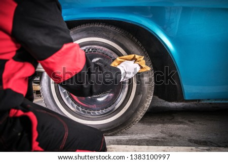 Classic Car Wheels Care. Professional Automotive Worker Cleaning Tire Using Specialized Spray.