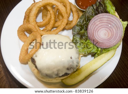 classic cheeseburger onion rings kosher pickle slice or red onion lettuce ketchup plate - stock photo