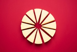 Classic cheesecake sliced in equal portions, isolated on red background. Top view of sliced creamy cheesecake. Homemade delicious Christmas dessert.