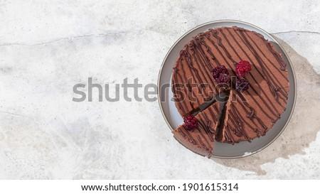 Classic chocolate cheesecake on light gray concrete background. Homemade baking. Vegan sugar gluten free dessert. Top view. Zdjęcia stock ©