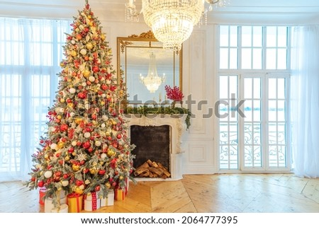 Classic Christmas decorated interior room, New year tree with red and gold decorations. Modern white classical style interior design apartment with fireplace and Christmas tree. Christmas eve at home