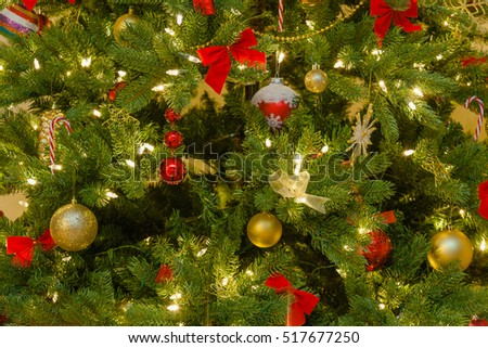 classic christmas decorations in red and golden yellow on pine tree in evening light close