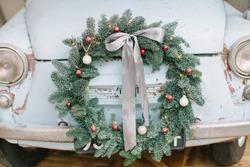 Classic christmas wreath on blue retro car. Holiday car wreath. Retro car decorated with christmas wreath for holidays.