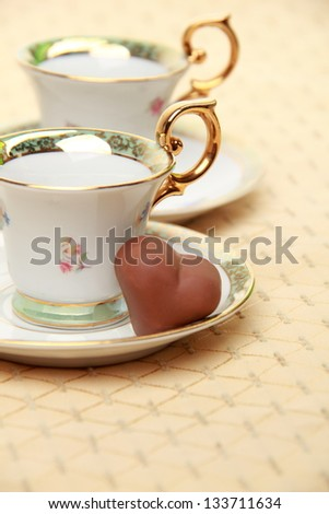 Classic coffee cup  chocolate candy on the beige tablecloth on Food and Drink