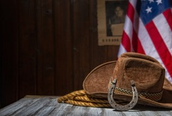 Classic cowboy hat and lasso lie on a wooden table against the background of the US flag and the poster for the search for the criminal in the sheriff's office