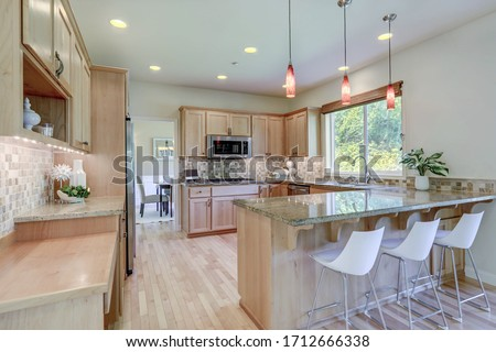Classic cozy bright kitchen interior with wooden cabinets and granite grey green countertops.