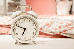 Classic design white alarm clock showing time about seven in morning on background of bed linen pink pastel shades. Happy morning concept, early rise, bedroom interior detail. Space for text.