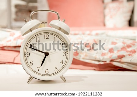 Classic design white alarm clock showing time about seven in morning on background of bed linen pink pastel shades. Happy morning concept, early rise, bedroom interior detail. Space for text. Photo stock ©