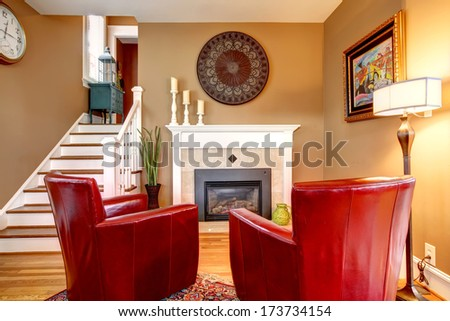 Classic designed family room with comfortable red chairs, light tones fireplace, hardwood floor and beige walls