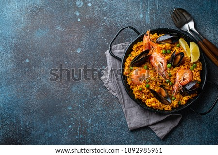 Classic dish of Spain, seafood paella in traditional pan on blue stone background top view. Spanish paella with shrimps, clamps, mussels, green peas and fresh lemon wedges from above, space for text