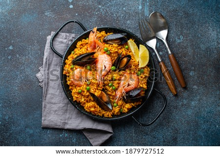 Classic dish of Spain, seafood paella in traditional pan on rustic blue concrete background top view. Spanish paella with shrimps, clamps, mussels, green peas and fresh lemon wedges from above