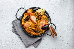 Classic dish of Spain, seafood paella in traditional pan on white wooden background top view. Spanish paella with shrimps, clamps, mussels, green peas and fresh lemon wedges from above
