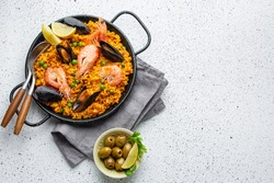 Classic dish of Spain, seafood paella in traditional pan on white wooden background top view. Spanish paella with shrimps, clamps, mussels, green peas, fresh lemon wedges from above, space for text