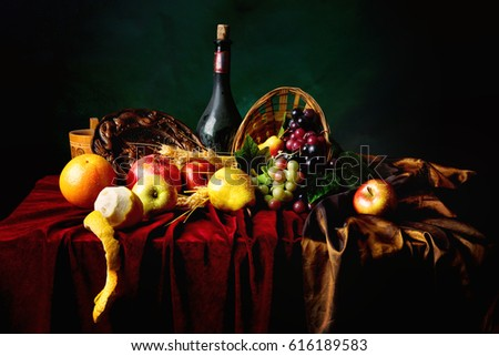 Classic Dutch still life with dusty bottle of wine and fruits on a dark green background, horizontal.