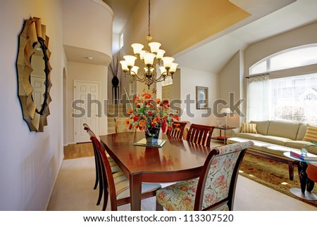Classic elegant dining room with living room and high ceiling and large window.
