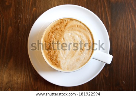 Classic foamy cappuccino in on a dark grained wood table. Detail. From above.