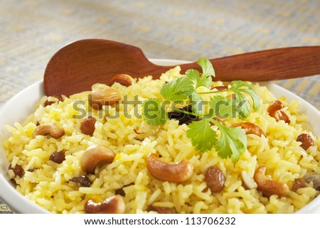 Classic fruit and nut Indian pilau, basmati rice cooked with stock, saffron, garlic, onion, cinnamon, cardamom, sultanas and garnished with cashew nuts and coriander. Focus on centre.