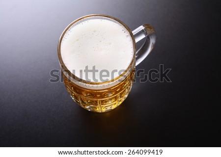 Classic glass mug full of light lager beer shot topdown over a dark background
