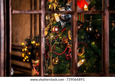 Classic green new year tree with flashing garland in the dark room. Christmas interior background, view through the window