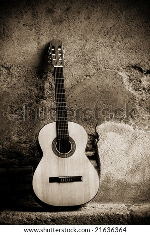 Classic guitar on wall, sepia toned.