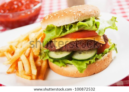 Classic hamburger served on a plate with french fries