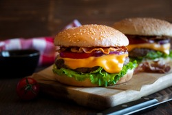 Classic hamburgers with cheese, bacon, tomato and lettuce on dark wooden background