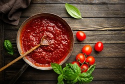Classic homemade Italian tomato sauce with basil for pasta and pizza in the pan on wooden background, top view.