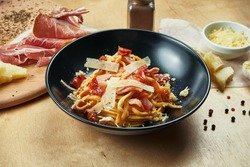 Classic, homemade pasta with red sauce, parmesan, ham and sun-dried tomatoes in black bowl. Traditional italian cuisine
