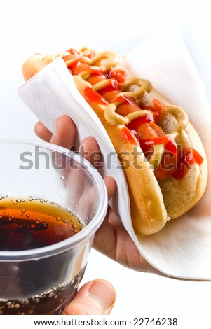 classic hot dog with mustard and ketchup and cola in hands