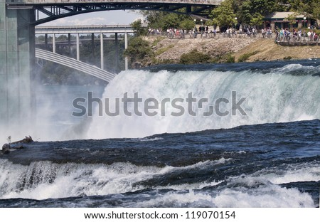 Classic image of Niagara Falls taken from Goat Island on the New York Side of the Niagara River. The image shows water rushing over the American Falls; the Observation Deck is visible in distance.