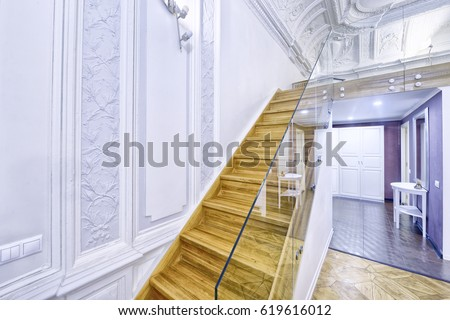 Classic interior design duplex apartment with white wall and ceiling moldings. Design of stairs in a rich house. #619616012