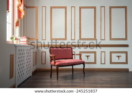 Classic interior design Elegant interior in red and golden colors with a vintage couch standing against the wall decorated with golden moldings in day light