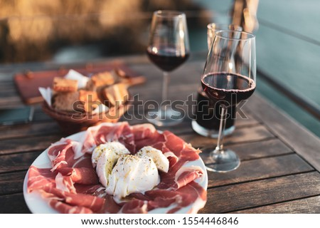 Classic italian antipasti with red wine and sea in background Stock photo ©