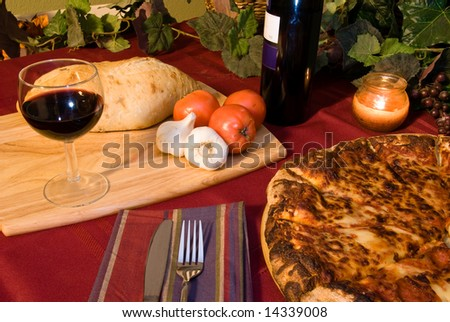 Classic Italian food setting with wine, pizza, bread and trimmings.