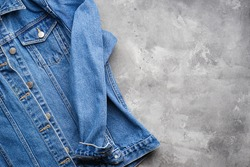 Classic jeans texture. Blue denim jacket on a gray background, space for text. Top view.
