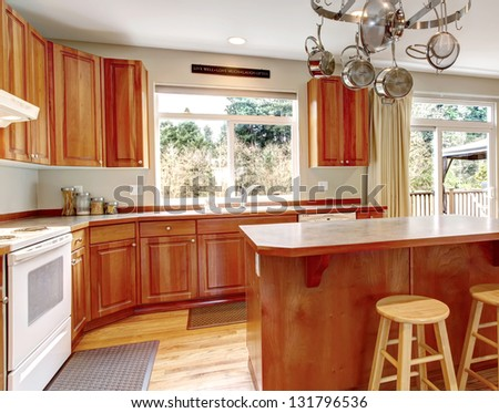 Classic large wood kitchen interior with hardwood floor, breakfast table.