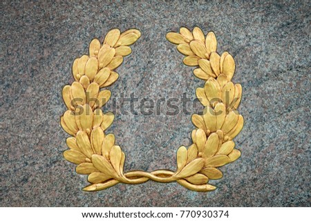 Classic laurel wreath symbol with vintage gold leaf detail on textured raised relief against a smooth gray stone background #770930374