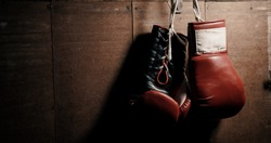Classic, leather, oldschool, red boxing gloves hanging on the wall. Vintage, retro style.